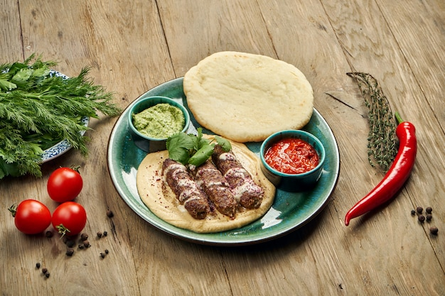 Appetizing rolls of lyulya kebab - cooked over a lamb minced meat with a side dish of hummus with pita and salsa on ceramic plate. vertical, wooden table, eastern cuisine
