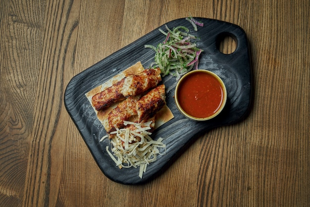 Appetizing rolls of lyulya kebab - cooked over a lamb minced meat with a side dish pita and salsa on wooden tray. wooden surface, eastern cuisine. top view