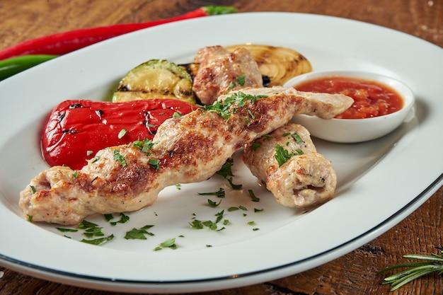 Аппетитные рулетики из люля кебаб - приготовленные из куриного фарша в белой тарелке с овощами гриль. деревянный стол