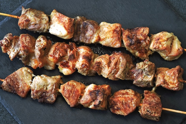 Appetizing ruddy kebabs on a dark stone surface. top view.