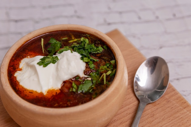 Appetizing russian borsch with sour cream and green pepper in a clay bowl on a wooden board. a popular dish of national cuisine. space for text.