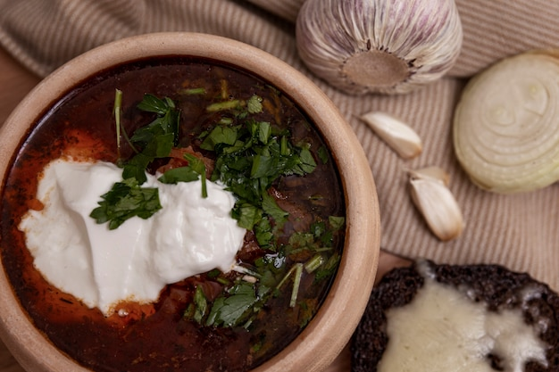 Appetizing russian borsch with sour cream and green pepper in a clay bowl on a wooden board. served with garlic and onions. a popular dish of national cuisine.
