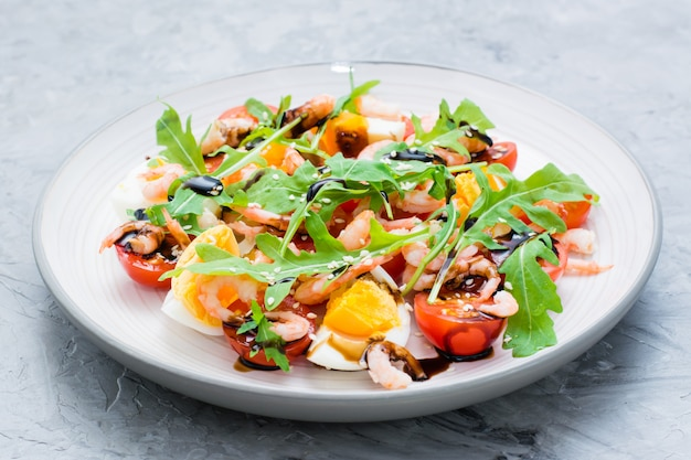Appetizing salad of cherry tomatoes, eggs, boiled shrimps, arugula, sesame seeds and balsamic sauce in a plate
