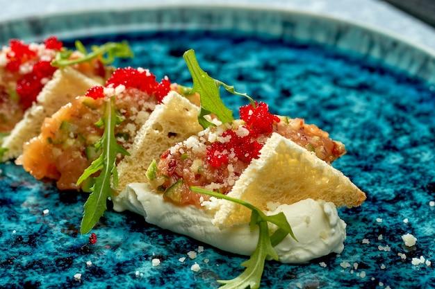 Аппетитный салат - тартар из лосося с белой эспумой, рукколой, гренками и икрой тобико в голубой тарелке на голубом фоне
