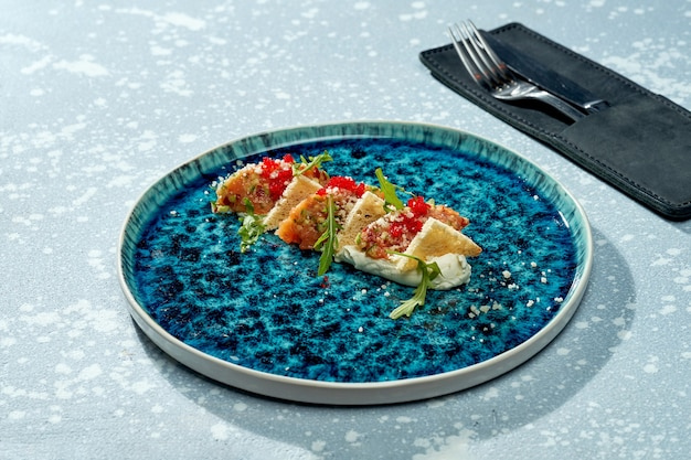 Аппетитный салат - тартар из лосося с белой эспумой, рукколой, гренками и икрой тобико в синей тарелке на голубой поверхности