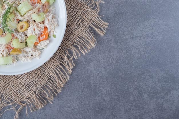 Аппетитный салат с курицей на белой тарелке.