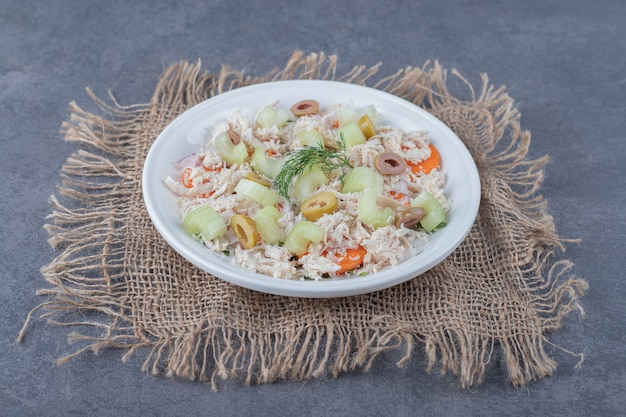 Insalata appetitosa con pollo sul piatto bianco.