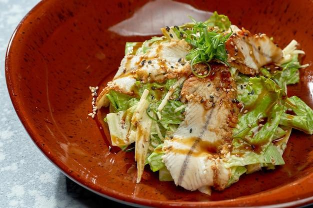 Аппетитный салат с угрем, соусом терияки, листьями салата в красной тарелке на синем фоне