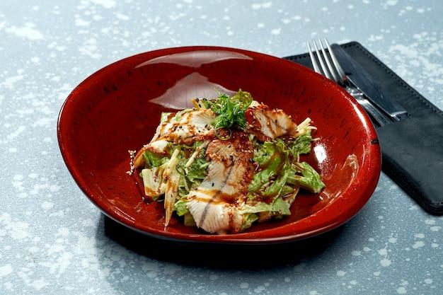 파란색 표면에 빨간 접시에 장어, 데리야끼 소스, 양상추와 함께 식욕을 돋우는 샐러드
