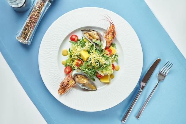 青いテーブルクロスの白いプレートにシーフード、アカザエビまたはエビ、ムール貝、ルッコラ、チェリートマトの食欲をそそるサラダ