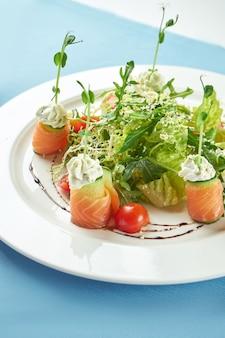 青いテーブルクロスの白いプレートにシーフード、サーモン、ルッコラ、チェリートマトの食欲をそそるサラダ