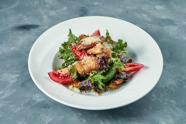 白い皿にトマト、ルッコラ、七面鳥のグリルの食欲をそそるサラダ。コンクリート表面
