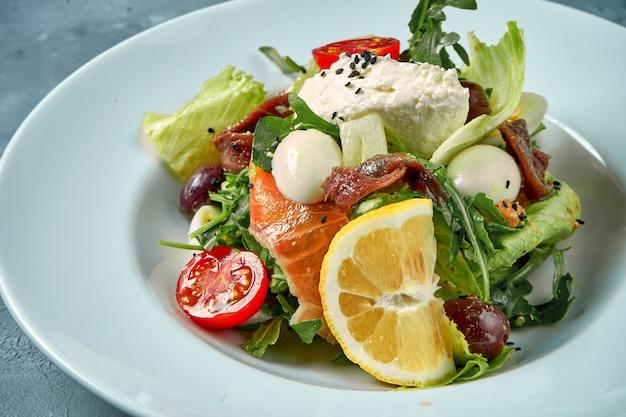 Аппетитный салат с помидорами, лососем, анчоусами и сливочным сыром в белой тарелке на бетоне