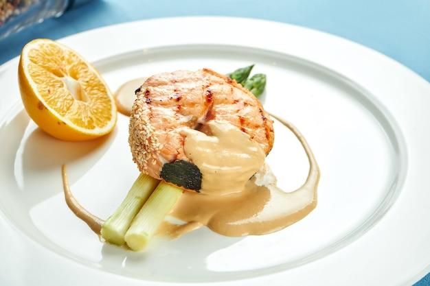 아스파라거스와 블루 식탁보에 하얀 접시에 소스와 함께 식욕을 돋 우는 연어 스테이크.