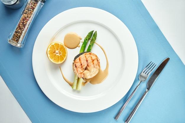 Аппетитный стейк из лосося со спаржей и соусом в белой тарелке на синей скатерти.