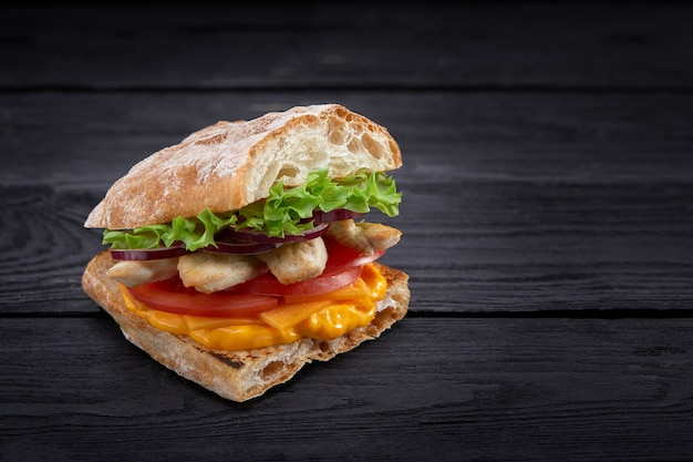 Appetizing sandwich on a wooden board. baguette sandwich with filling from lettuce, slices tomato. dark wooden background. view from above. close-up. macro photography.