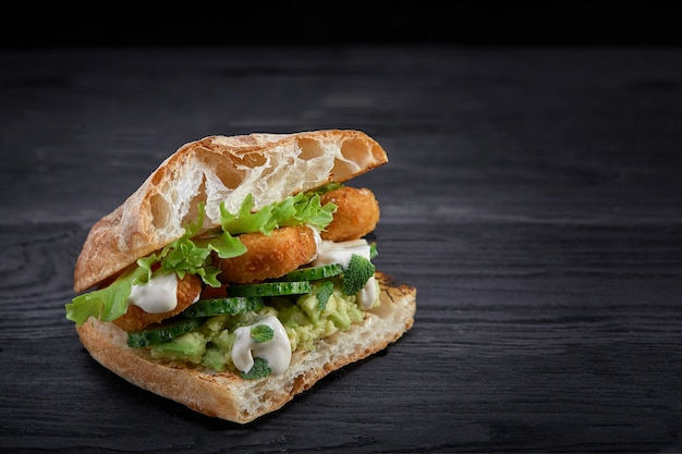 Appetizing sandwich on a wooden board. baguette sandwich with filling from lettuce, slices tomato.