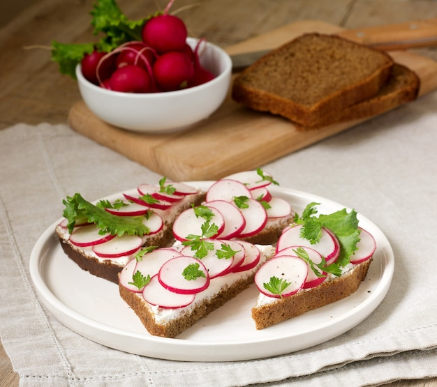 Appetizing sandwiches of rye bread with curd cheese, radishes and lettuce. rustic style.