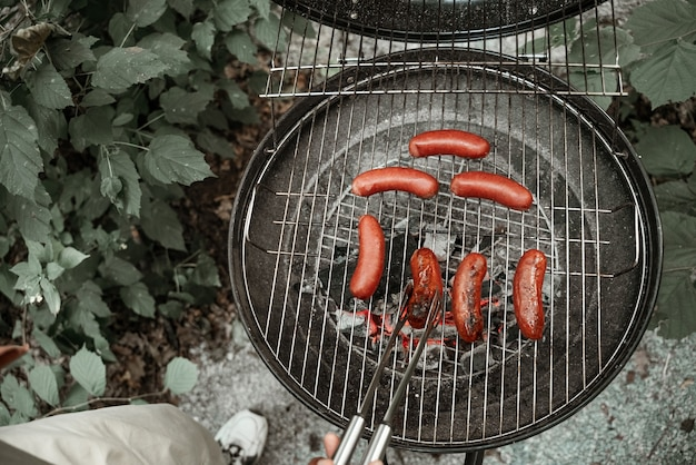 炭火焼きで焼く食欲をそそるソーセージ。グリルソーセージに触れるフォークで手。バーベキューパーティー。キャンプフード、不健康な食べ物。新鮮な空気の下でのピクニック。