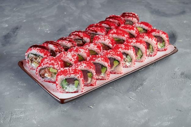 Аппетитный набор калифорнийских суши-роллов в красной икре тобико с лососем, тунцом и угрем в белой тарелке на сером