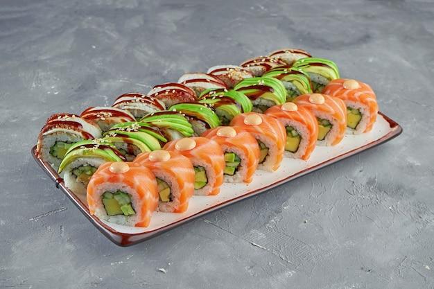 Аппетитный набор суши-роллов дракон с лососем, авокадо и угрем в белой тарелке на сером