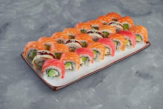 Аппетитный набор суши-роллов филадельфия в красной икре тобико с лососем, тунцом и угрем в белой тарелке на сером