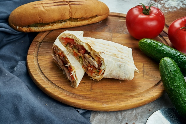 Аппетитная шаурма или шаурма с мясом, помидорами, капустой. мясо цыпленка. шашлык на деревянный поднос. крупным планом, селективный фокус
