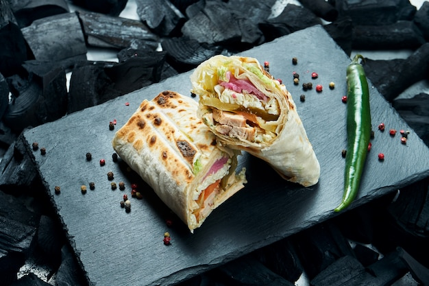 Appetizing shaurma or shawerma with spices and onions on a black slate tray on a surface of charcoal. kebab