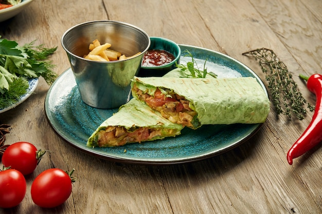 Appetizing shawarma roll with meat, salad and homemade sauce in thin pita bread in blue plate isolated in grey surface. eastern cuisine. sliced kebab with grilled meat.