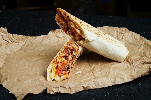 Appetizing shawarma roll with meat, salad and homemade sauce in thin pita bread on craft paper on a black surface. eastern cuisine. sliced kebab with grilled meat.
