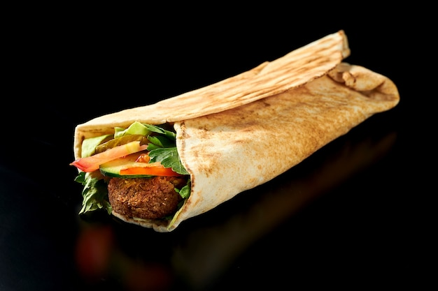 Appetizing shawarma with falafel, cucumbers, carrots and tomatoes in pita bread. black surface. isolated. close up, selective focus