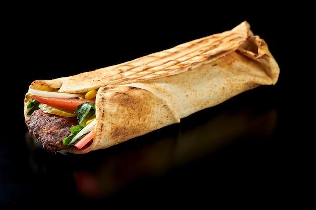 Аппетитная шаурма с люля-кебабом из баранины, огурцами, морковью и помидорами в лаваше. черная поверхность. изолированный. крупным планом, выборочный фокус