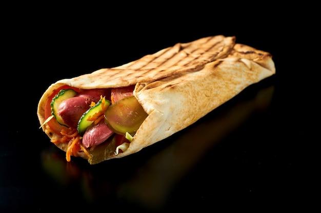 피타 빵에 훈제 소시지, 오이, 당근, 토마토를 곁들인 식욕을 돋우는 샤와 마. 검은 색 표면. 외딴. 클로즈업, 선택적 초점