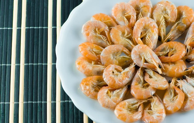 Appetizing shrimps in a white plate lie on a blue napkin in the restaurant