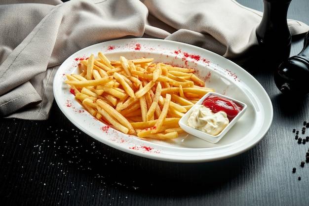 Аппетитный гарнир - картофель фри с майонезом и кетчупом в белой тарелке.