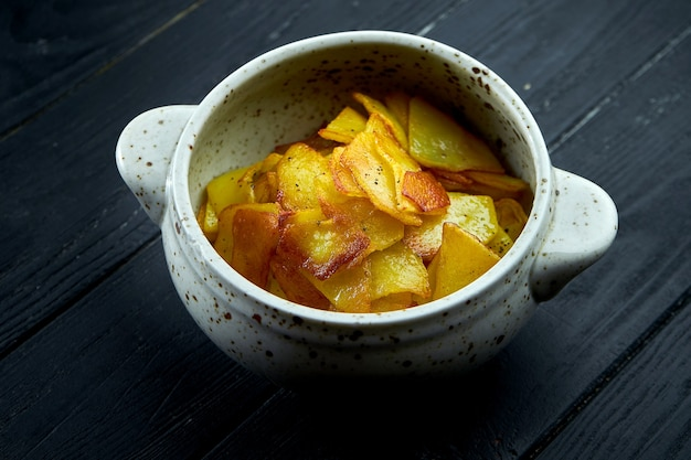 Appetizing side dish - fried potatoes with onions served in a white bowl on a dark background.