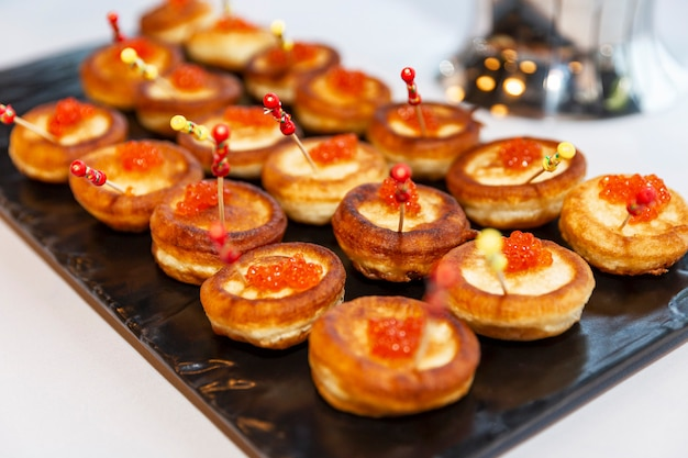 Appetizing snacks on the buffet table at the event. canapes with red caviar. close-up.