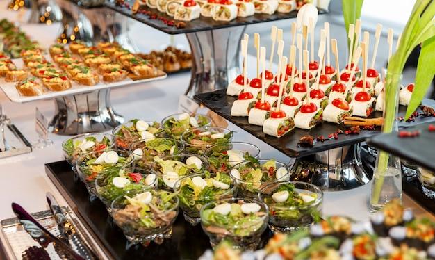 Аппетитные закуски на фуршете на мероприятии. крупный план. Premium Фотографии
