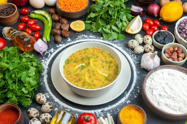 Zuppa appetitosa servita con limone e verde in una ciotola bianca e farina di pomodoro olio bottiglia farina verde fasci uova al buio