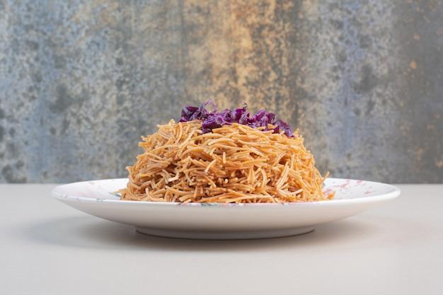 皿に刻んだキャベツを添えた食欲をそそるスパゲッティ。