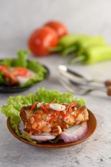 食欲をそそるスパイシーな缶詰イワシのサラダ、木製ボウルのスパイシーソース添え
