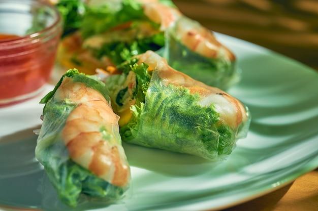 하얀 접시에 야채와 새우를 넣은 식욕을 돋우는 춘권. 나무 배경입니다. 중국 요리