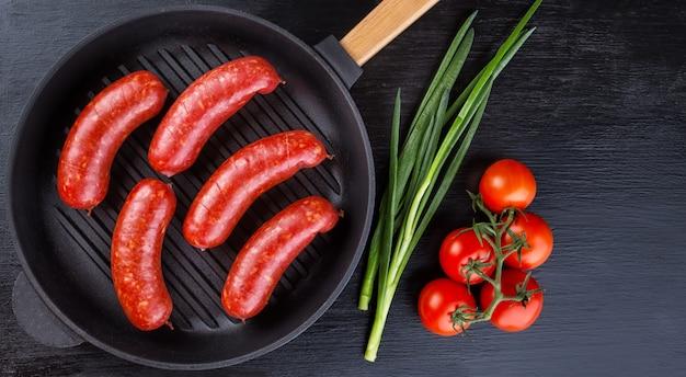 Аппетитные сочные колбаски в чугунной сковороде с