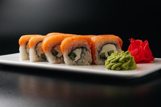 Аппетитный суши-ролл филадельфия с сырным огурцом и лососем на черном фоне
