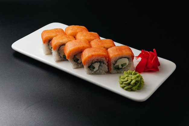Appetizing sushi roll philadelphia with cheese cucumber and salmon on black background