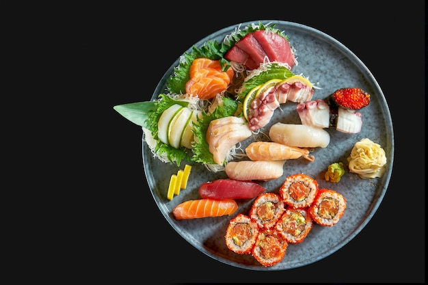 An appetizing sushi set consisting of various nigiri. sashimi and uramaki with salmon, avocado and tobiko caviar. japanese traditional cuisine. food delivery. isolated on black