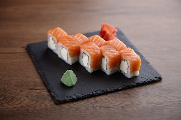 Appetizing sushi set on a stone plate on a dark wooden table