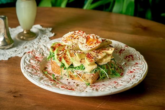Аппетитный бутерброд с тостами: хлеб, авокадо, сливочный сыр, камамбер, помидоры черри, микрозелень, яйцо.