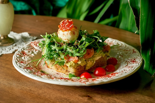 Аппетитный бутерброд с тостами: хлеб, авокадо, сливочный сыр, помидоры черри, лосось, руккола, микрозелень, яйцо, красная икра.