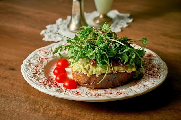 Аппетитный бутерброд с тостами: хлеб, авокадо, сливочный сыр, мини-моцарелла, вяленые помидоры, руккола, микрозелень.
